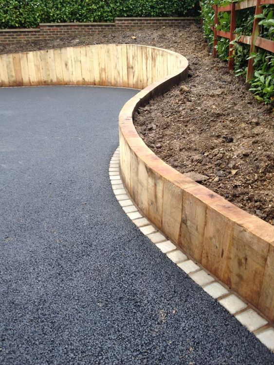a tall wooden border for the raised garden bed and asphalt gardne pathways for an ultra modern look