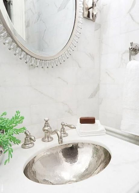 a Calcutte marble countertop with a silver hammered sink, matching marble tiles around and a mirror in a silver frame