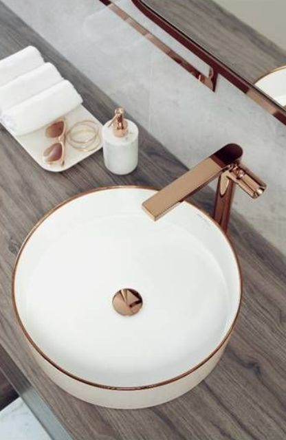 a chic round vessel sink with a copper rim and center plus a matching faucet is a beautiful and elegant option