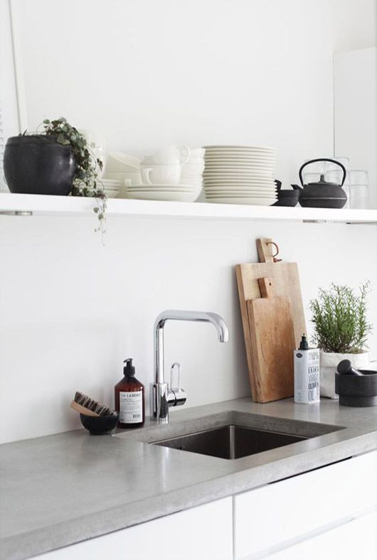 a concrete countertop and a neutral kitchen sink make up a chic and bold combo for a minimalist kitchen