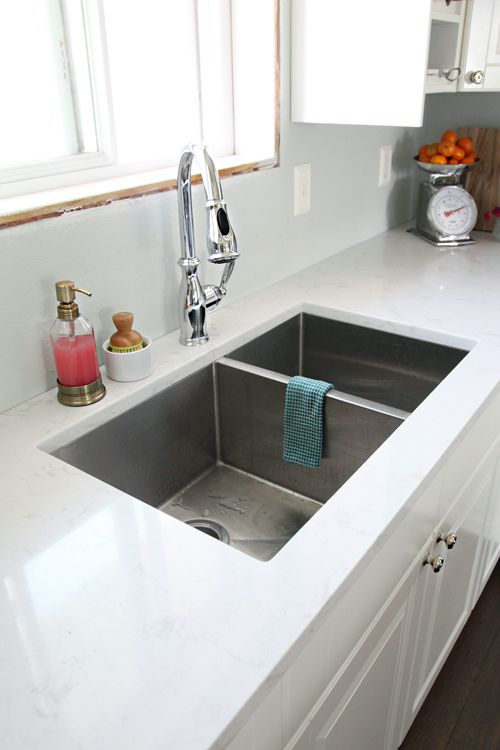 a contemporary undermount sink with two parts installed into a white stone countertop is ideal for a modern farmhouse kitchen