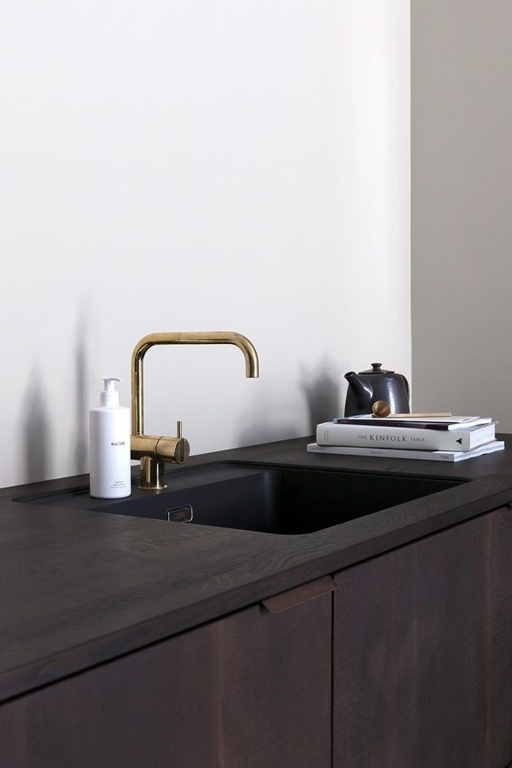 a dark cabinet with an undermount sink and a brass faucet is a chic idea that guarantees a sleek look