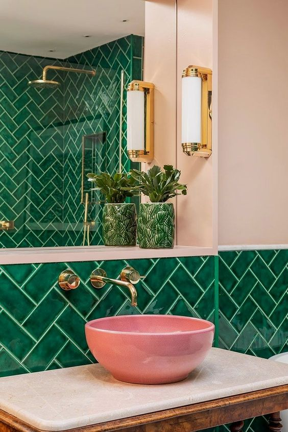 a glossy pink vessel sink adds an unexpected touch to this bright green bathroom, and gold touches brighten the space up