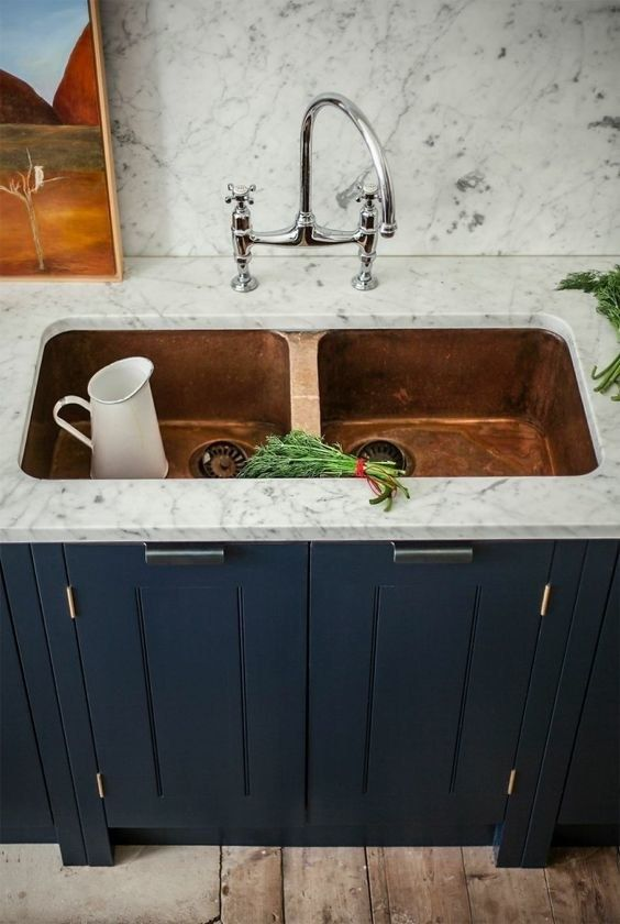 a gorgeous double copper sink in a white stone countertop look chic, especially with a navy cabinet