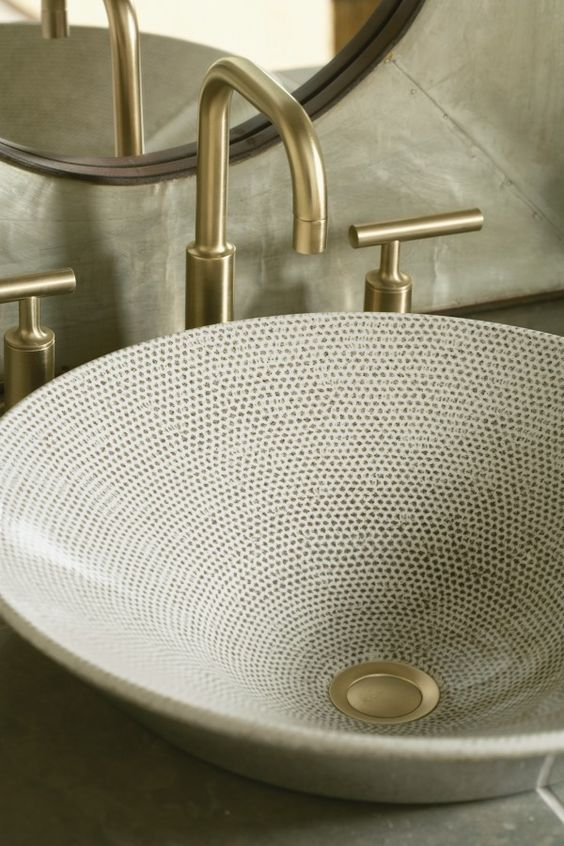 a large round sink with hand painting creates a feeling of a texture and brass touches make it look brighter and bolder