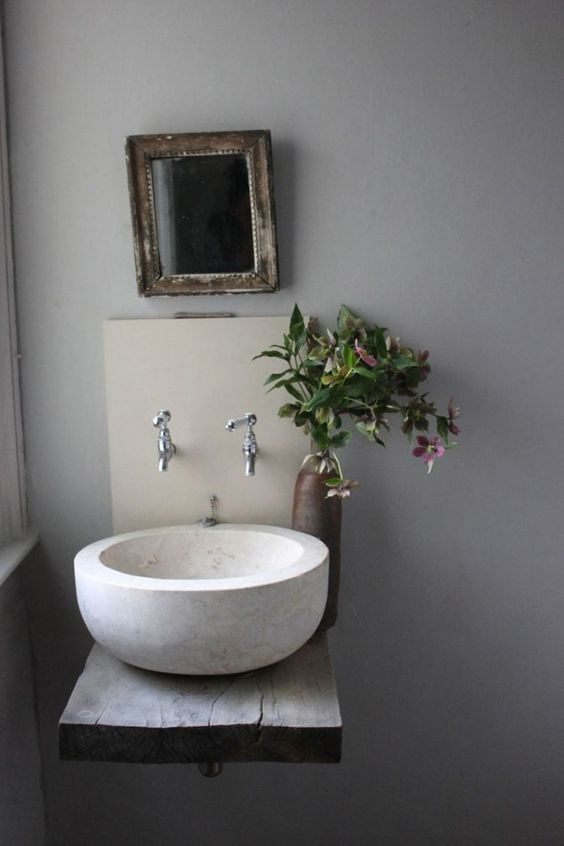 a large white stone vessel sink on a wall-mounted dough wood vanity is a cool rustic item