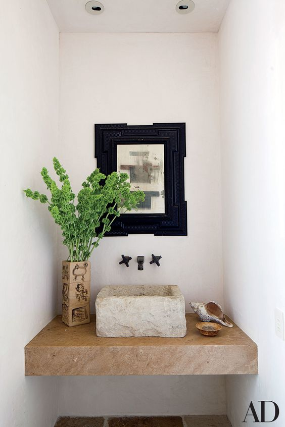 a rough stone square vessel sink on a stone built-in vanity is a gorgeous idea for an Italin villa