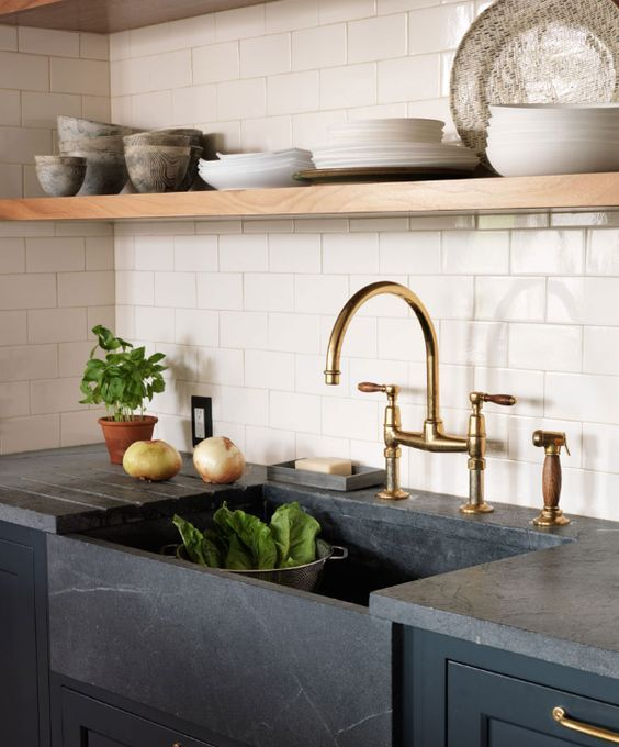 a soapstone undermount sink and a matching countertop for a chic moody farmhouse kitchen