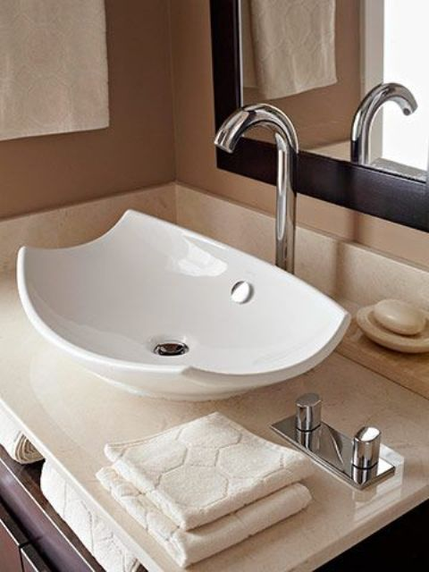 a stylish curved up white vessel sink adds a contemporary feel to the space with its curved corners