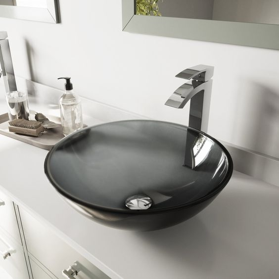 a stylish sheer black glass vessel sink looks very contemporary and a sculptural faucet increases this effect