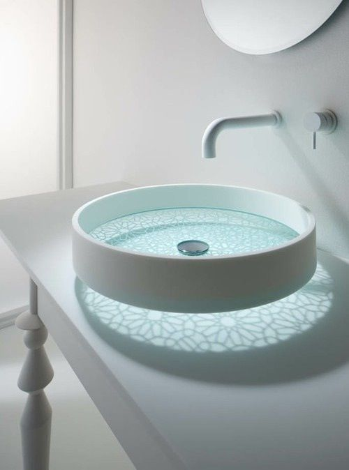 a unique sheer glass bathroom vessel sink with a beautiful painted bottom and light that comes through it