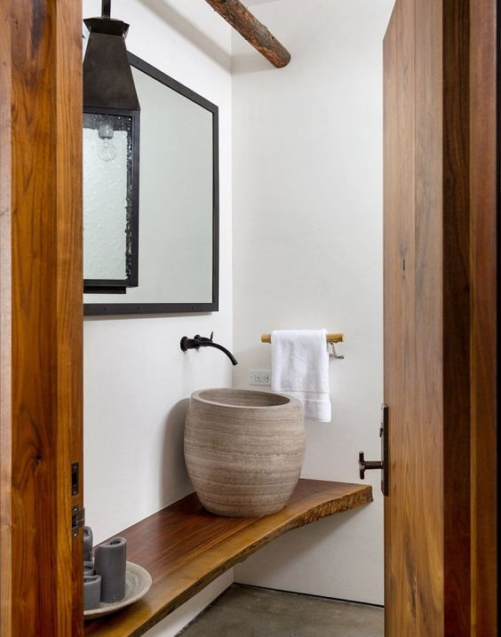 a unique tall vase-like vessel sink is ideal for a wabi-sabi or spa-inspired space