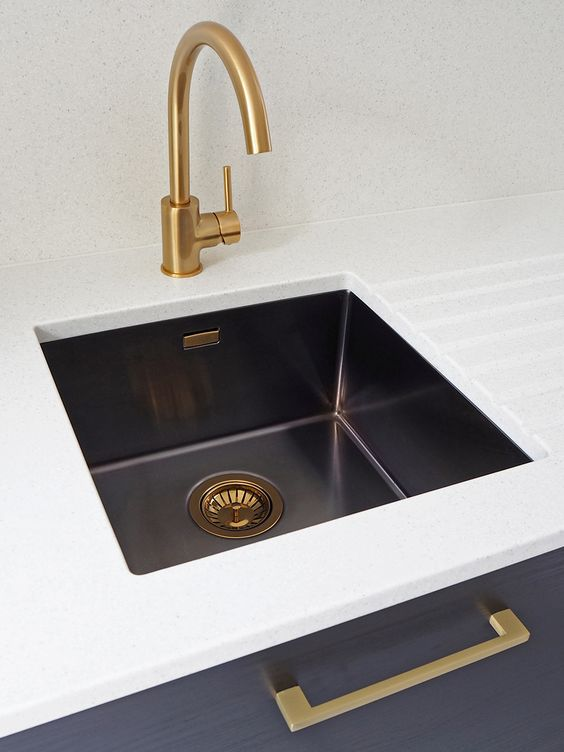 a white and navy vanity with a black undermount sink and brass and copper touches for a refined feel