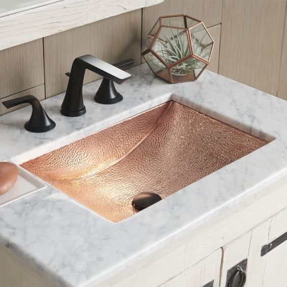 a white marble bathroom vanity with a hammered copper sink and matte black fixtures for a chic and glam look