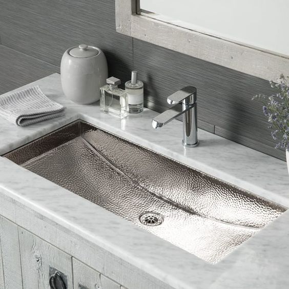 a white stone countertop and a polished hammered nickel sink for a neutral and fresh look in your bathroom