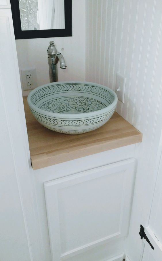 an aqua-colored vessel sink with hand painting adds a subtle touch of color and a vintage faucet is a perfect match
