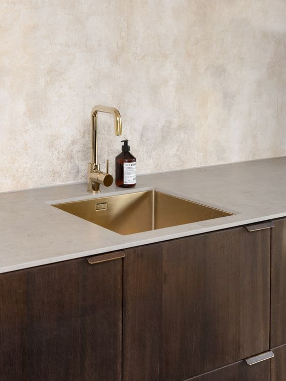give your kitchen a warm look with dark cabinets, a neutral countertop and a gold sink plus a gold faucet