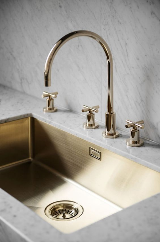 marble tiles and countertops plus a gold rectangurlar sink and gold fixtures is a touch of luxury in the space