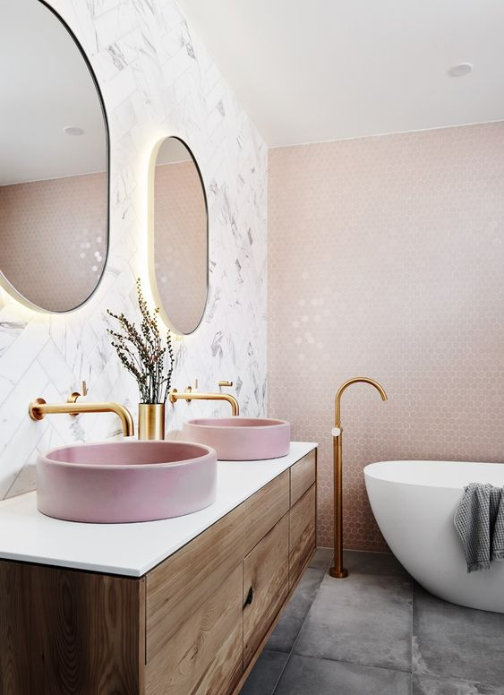 two round pink corian vessel sinks add color to the space and make it look more girlish