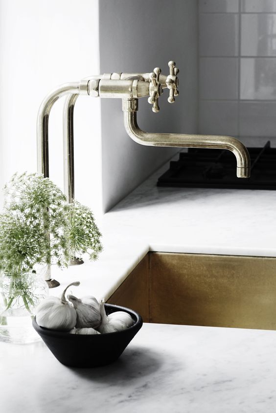 white stone countertops plus a gold undermount sink and a unique vintage faucet  for a touch of refined chic
