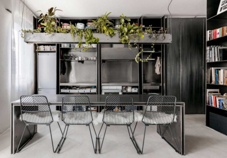 The kitchen is done with metal, all the appliances, a metal table and chairs plus a concrete planter over it
