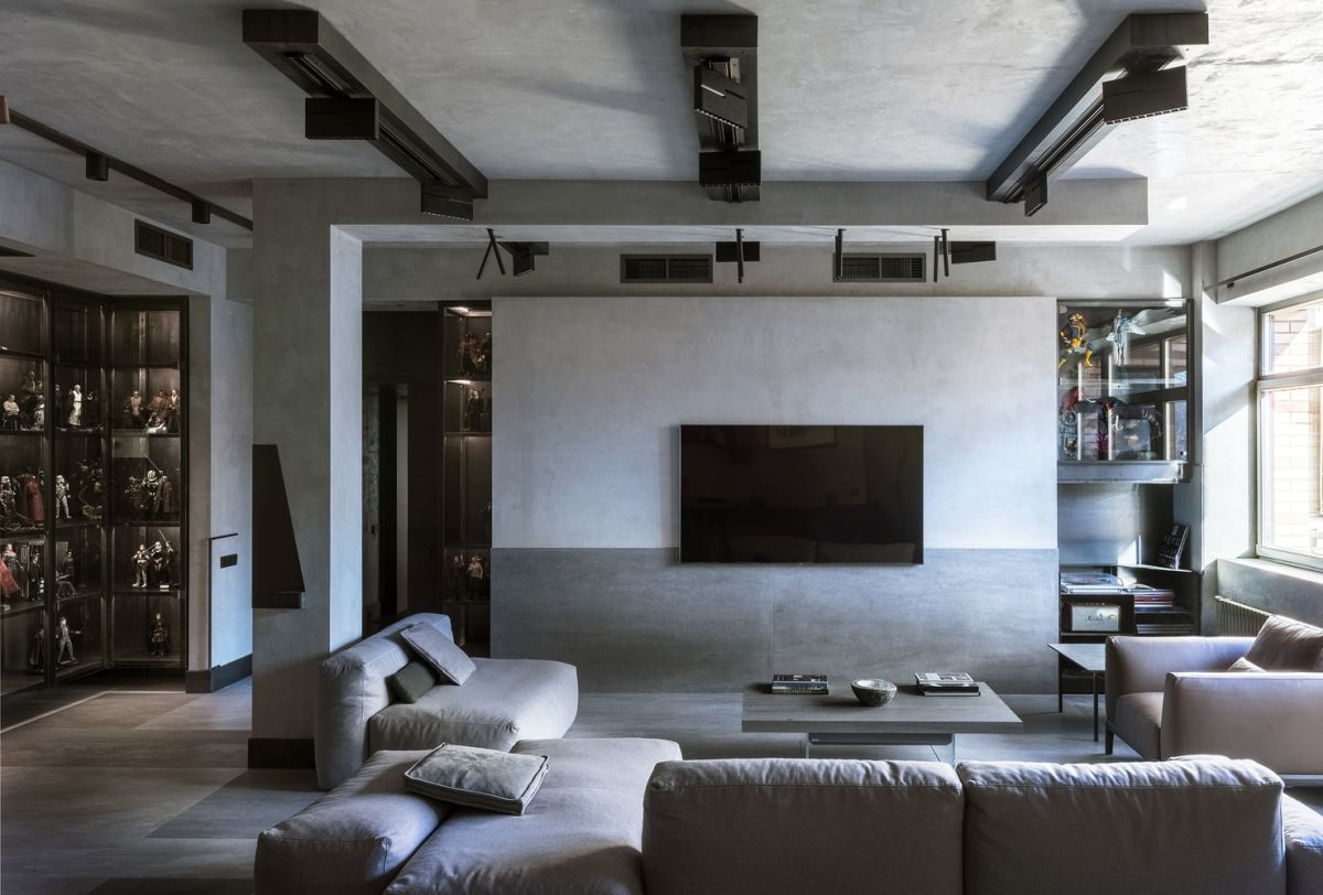 The living room features comfortable furniture, a minimalist coffee table and industrial lights on the ceiling