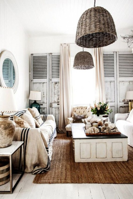 a beach cottage living room with wicker lamps over the space that add a cool coastal feel