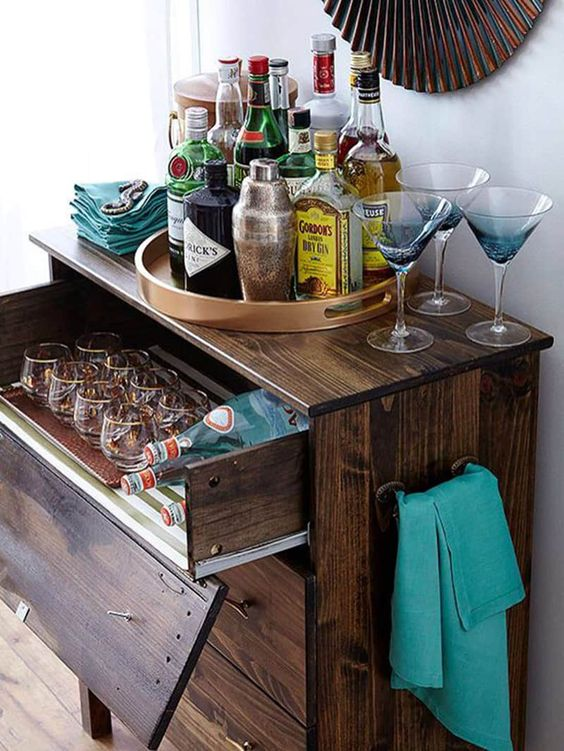 a dark stained IKEA Tarva dresser with a pullout drawer for stashing glasses and bottles is a chic rustic bar idea