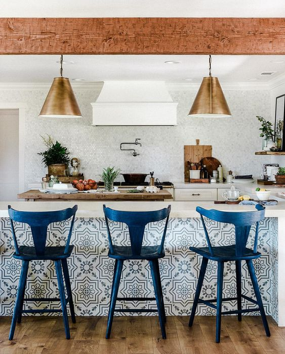 tall navy stools with a vintage design match the tiled kitchen island and give a refiend feel to the space