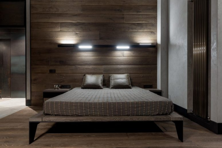 The bedroom shows off a wooden accent wall, a wooden bed with legs and some lights over the bed