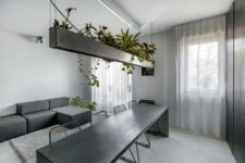 03 The living space continues the space with a laconic geometric sofa and potted plants