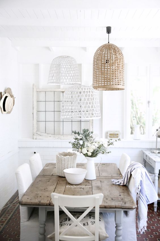 a beautiful dining space in white and neutrals and with several painted and non-painted wicker lampshades over it
