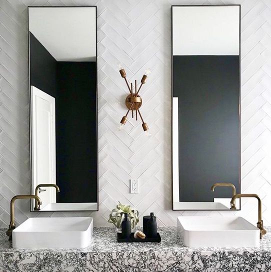 a bold art deco bathroom with white skinny tiles clad in a chevron pattern and a terrazzo floating vanity