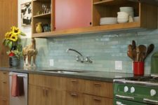03 a bright mid-century modern kitchen with red and green touches and mint green skinny tiles on the backsplash