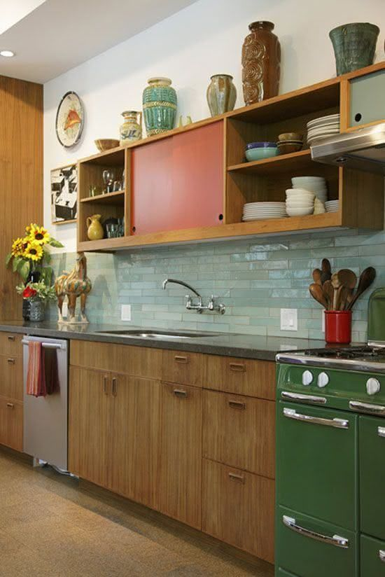 a bright mid-century modern kitchen with red and green touches and mint green skinny tiles on the backsplash
