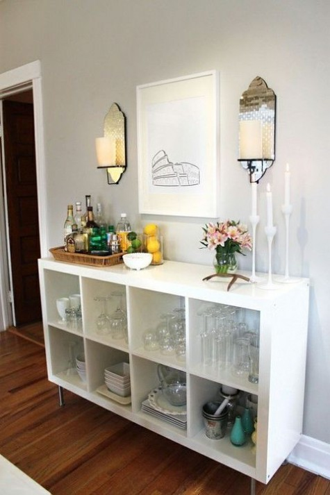 a chic home bar of an IKEA Kallax unit placed on legs features much storage space