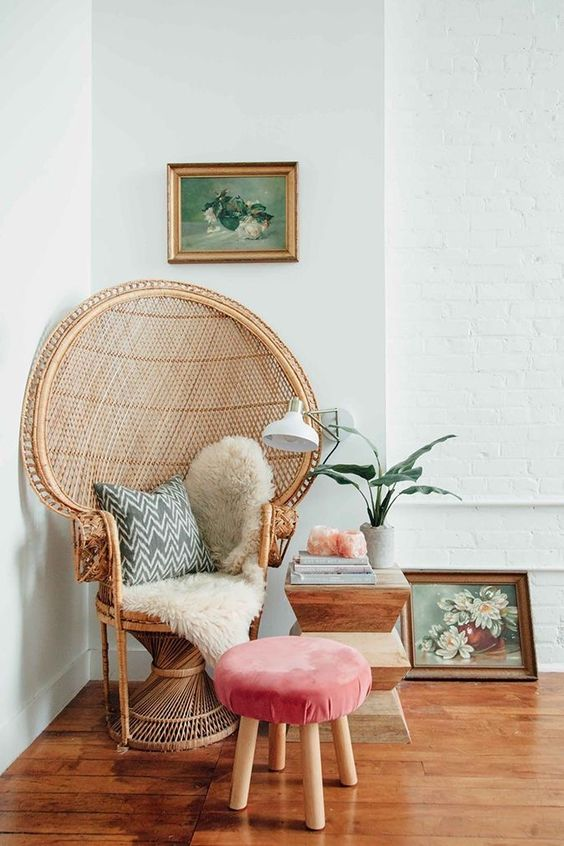 a peacock chair styled with faux fur, a pillow and a coral upholstered stool plus a side table create a gorgeous rest nook