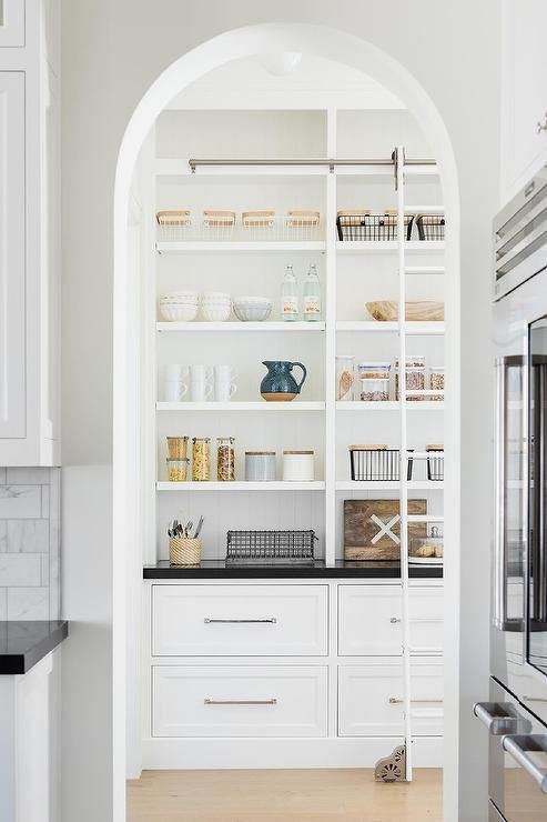 an arched doorway into a custom pantry featuring a ladder on rails on a built-in shelf with black quartz countertops