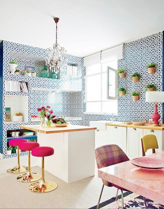 super bright pink stools with gold bases stand out in the blue and white kitchen and add a glam feel to the space