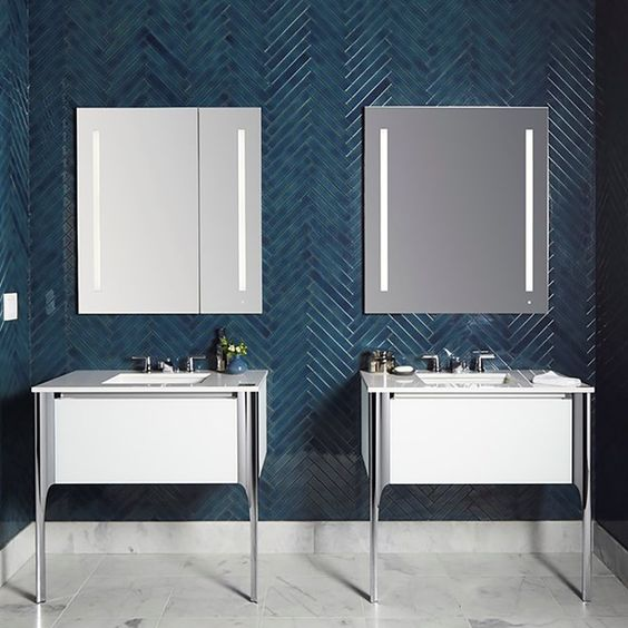 a bold contemporary bathroom wih teal skinny tiles clad in a chevron pattern and contrasting white vanities