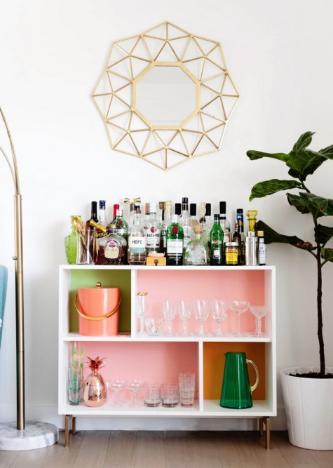 a bright home bar made of an IKEA Valje shelf with colored contact paper to spruce up the inside of each compartment