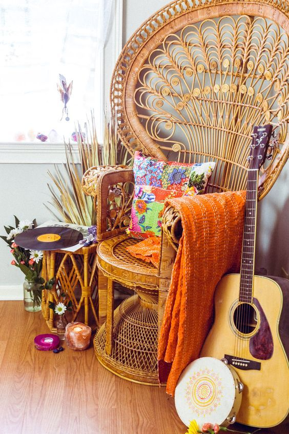 a colorful free-spirited nook with a peacock chair, bright textiles, a rattan side table, blooms and some musical instrument