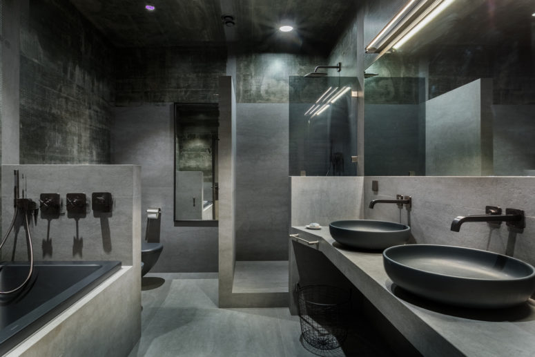 The bathroom is done with much concrete, stone and tiles, all in the shades of grey