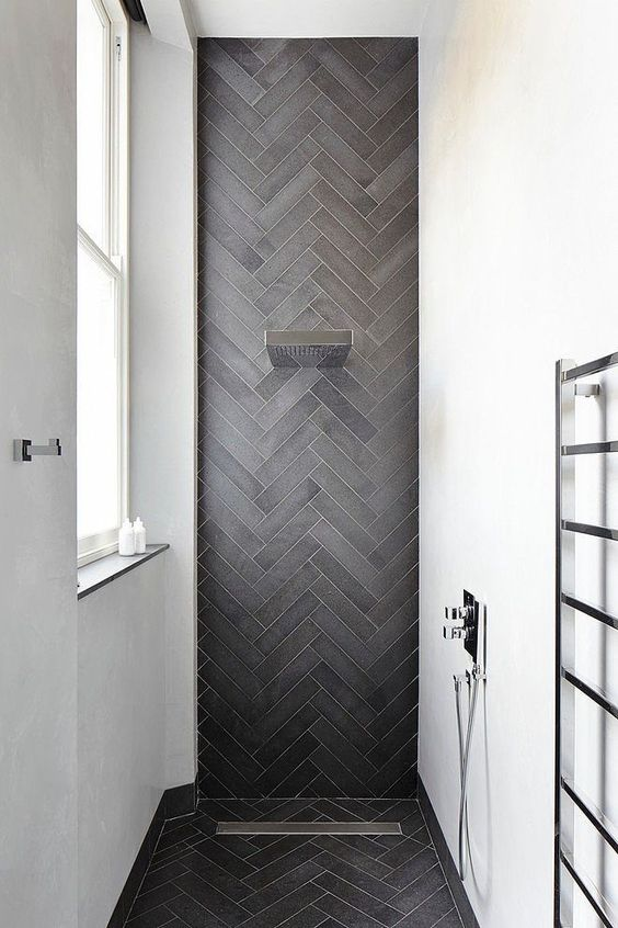 a chic contemporary shower space with white walls and an accent graphite grey skinny tiles clad in a chevron pattern and extended to the floor