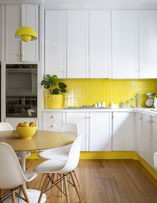a lemon yellow accented kitchen with white cabinets and a yellow skinny tile backsplash that echoes bright accents and touches