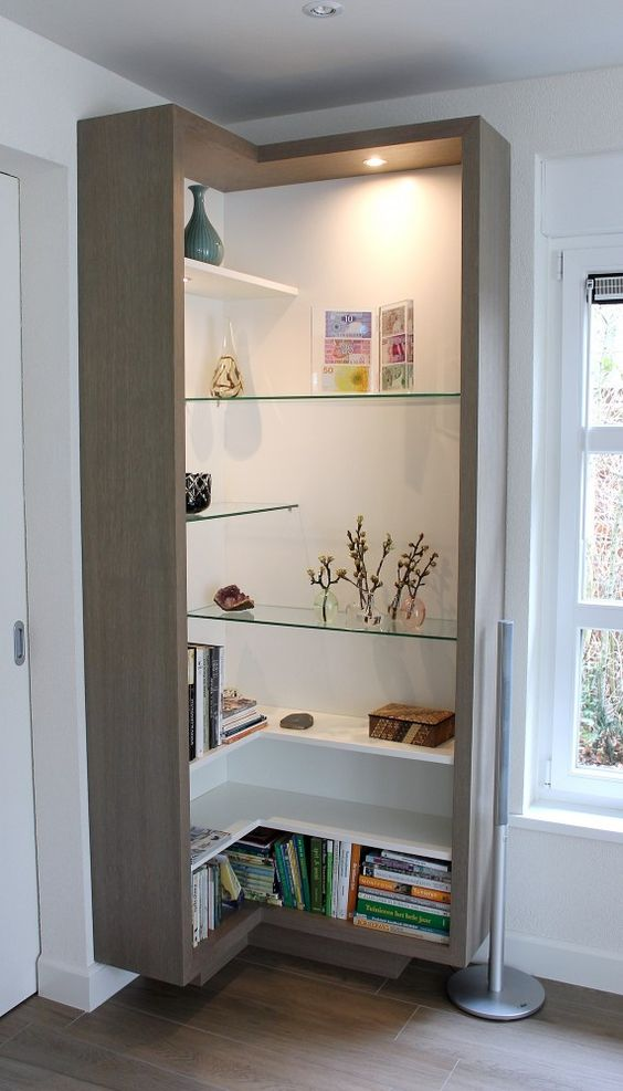 an open box shelving unit with sleek white and glass shelves located chaotically and with lights