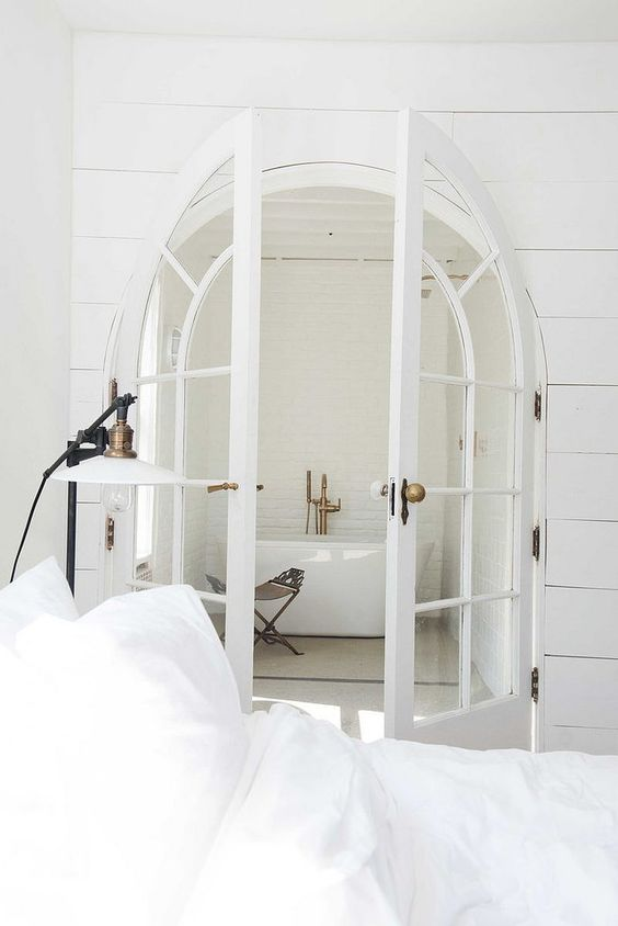 French arched doors leading to the bathroom make it more refined and chic at first glance
