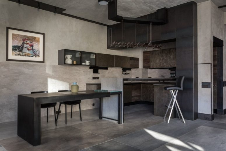 The kitchen is done in dark greys, with metal cabinets and a kitchen island that doubles as a dining space