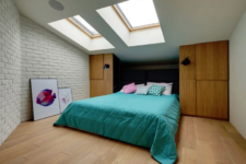 06 The second bedroom is smaller, it also features skylights, brick, storage units and a comfy bed