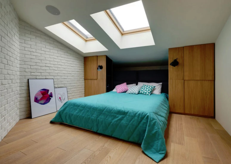 The second bedroom is smaller, it also features skylights, brick, storage units and a comfy bed